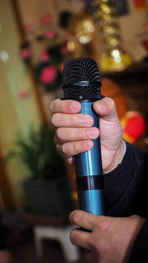 Male singer holding a wireless microphone during public performance