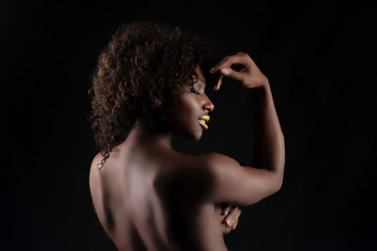 Close-up of shirtless young woman against black background