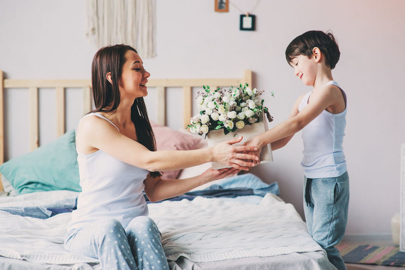 happy child boy giving flowers to mom in the morning for mothers day. Bed Sitting Indoors  Young Adult Women Two People Togetherness Young Women Casual Clothing Lifestyles Real People Bedroom Kid Toddler  Child Childhood Family Mom Motherhood Mothersday Flowers Gift Happy People Authentic Moments