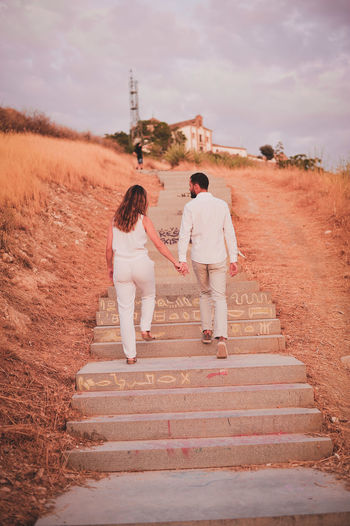 Rear view full length of young couple moving up on steps