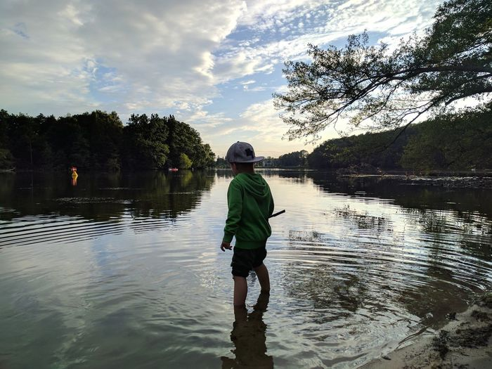 Rear view of boy standing in lake against sky