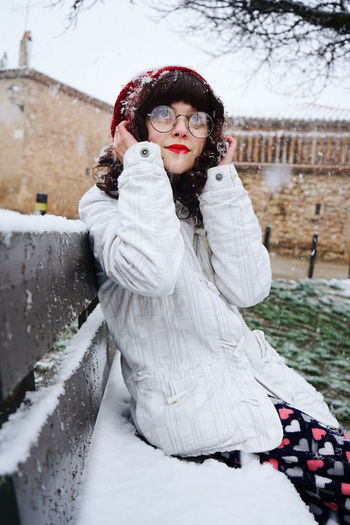 Young Woman Sitting On Snow Covered Bench Against Sky
