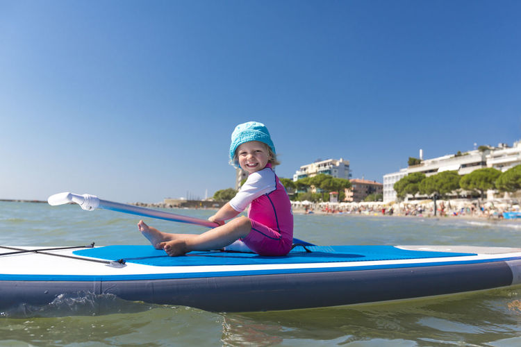Toddler sitting on a surfboard smiling Adorable Bibione Blonde Child Cute Côte D'Azur France Happy Having Fun Holiday Italy Jesolo Learning Sitting Smile SPAIN Surf Surfboard Surfer Surfing Swim Swimsuit Tarifa Toddler  Vacations