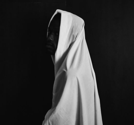 Close-up of person covering face against black background