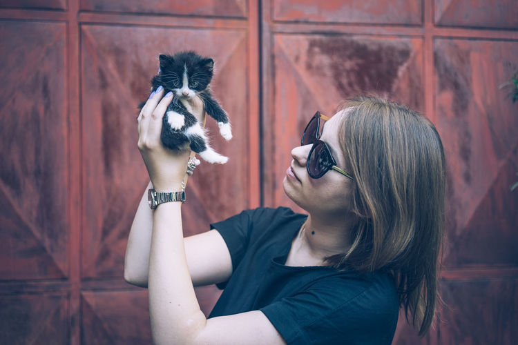 Young woman wearing sunglasses holding kitten in city