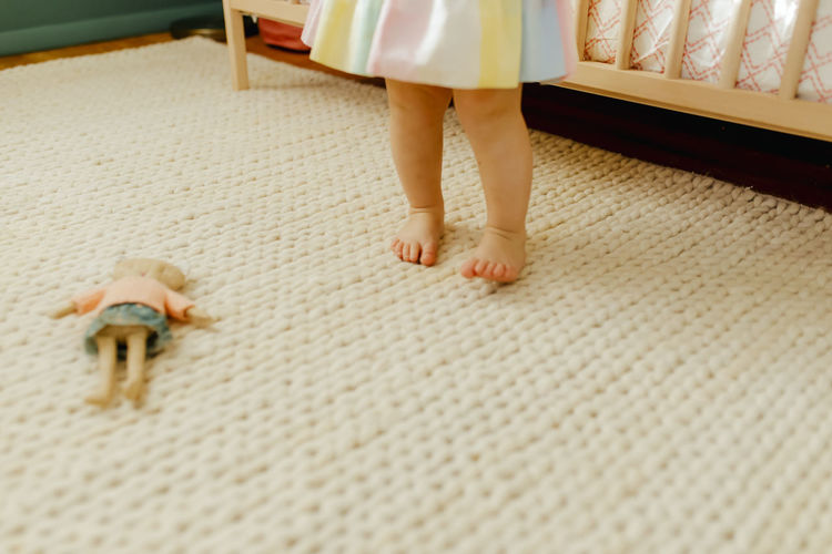 Low section of woman standing on carpet at home