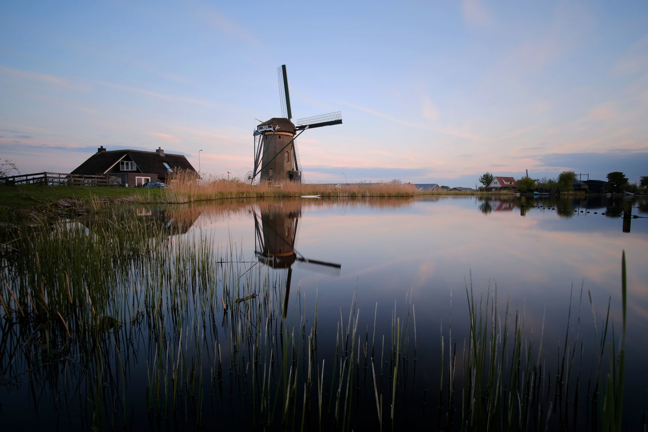 alternative energy, wind power, windmill, wind turbine, environmental conservation, renewable energy, built structure, fuel and power generation, architecture, water, reflection, traditional windmill, sunset, building exterior, no people, outdoors, nature, sky, industrial windmill, lake, grass, beauty in nature, scenics, rural scene, day, watermill