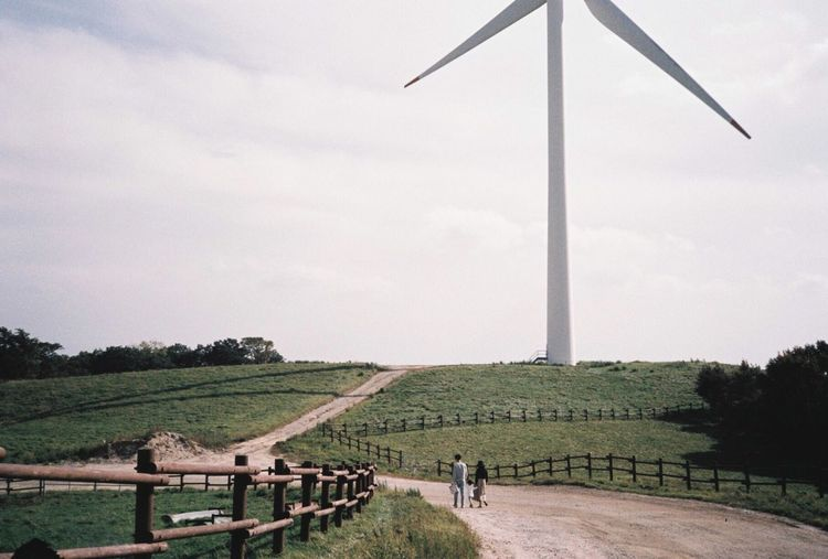 Parents walking with their child next to wind turbine