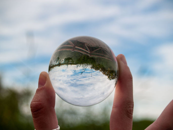 Cropped image of hand holding crystal ball against glass