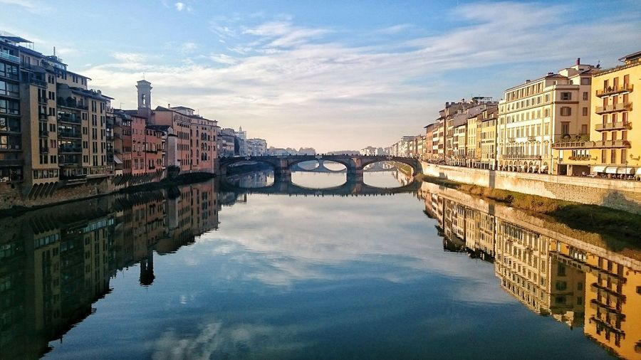 Bridge And Buildings Reflecting On Arno River In City