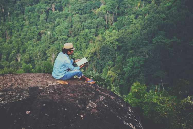 High angle view of man wearing hat sitting on cliff