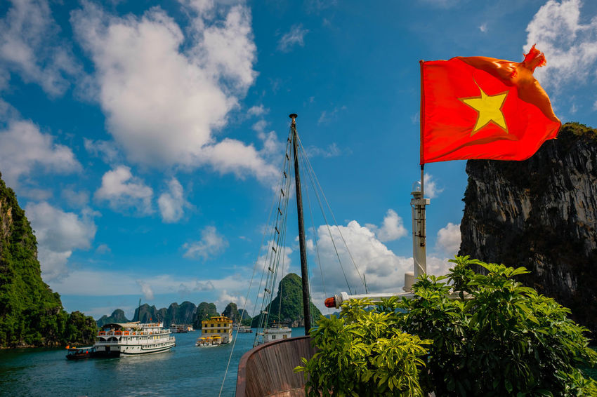 Floating along in Halong Bay Architecture Built Structure Cloud - Sky Day Flag Mode Of Transportation Nature Nautical Vessel No People Outdoors Patriotism Plant Red Sailboat Sky Transportation Tree Water Waterfront