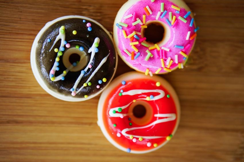 Food And Drink Food Sweet Food Sweet Donut Indulgence Indoors  Baked Multi Colored Wood - Material Dessert No People Unhealthy Eating Directly Above Still Life Close-up Ready-to-eat Table Sprinkles Icing Snack Medium Group Of Objects Temptation