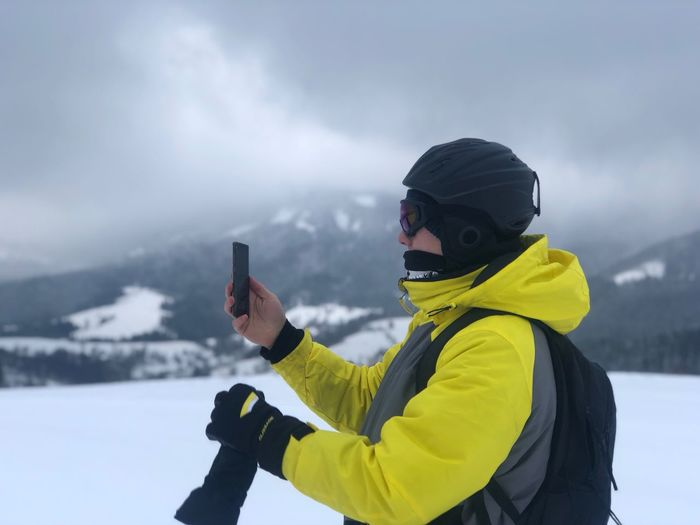 Side view of man photographing on snow covered land against sky