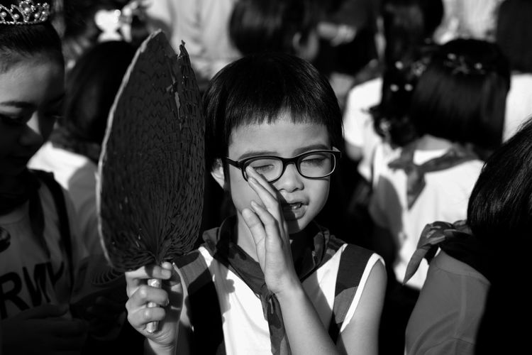 Boy with eyes closed holding hand fan amidst people