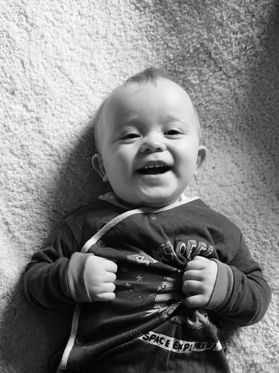 Directly above shot of happy baby boy relaxing on carpet