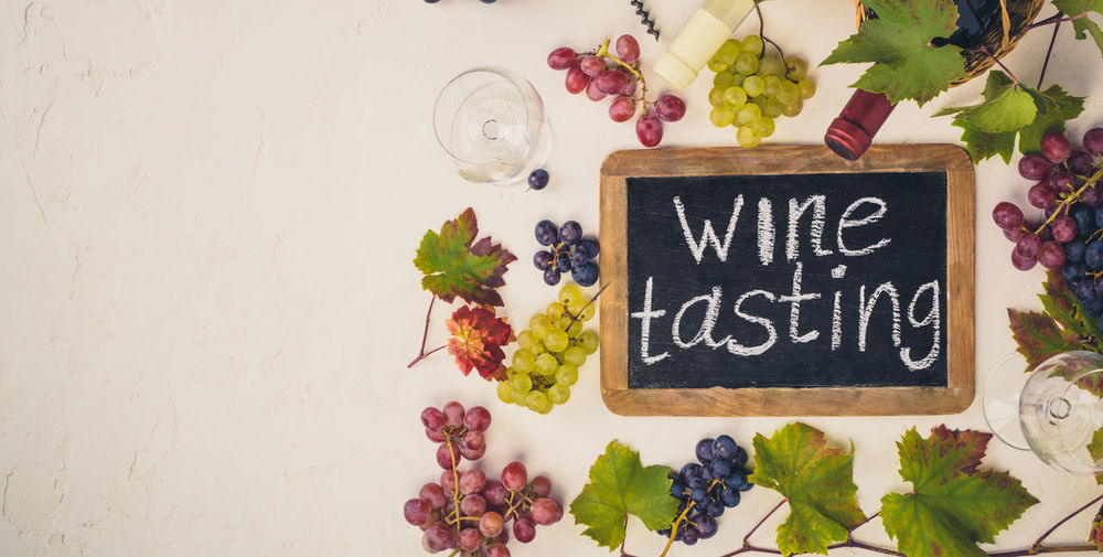 Directly above shot of winetasting text on slate with grapes on table