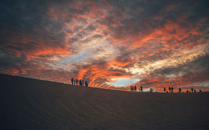 Silhouette Of People On Sand Dune During Sunset