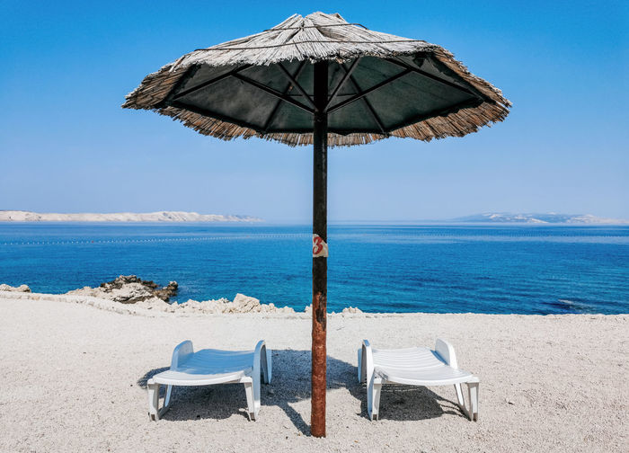 Empty deck chairs under straw parasol on beach on sunny day in summer.