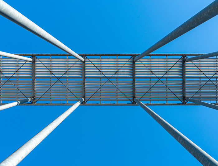 Low angle view of metallic structure against blue sky