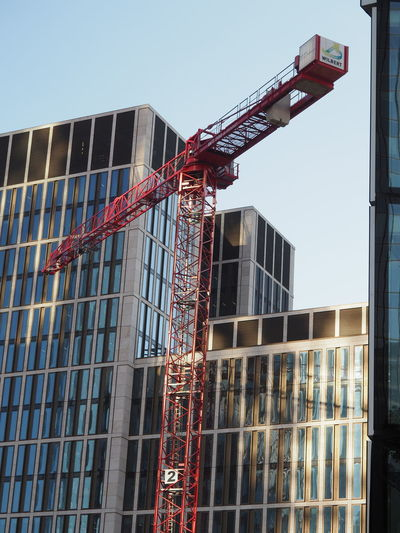 Architecture Building Exterior Built Structure City Construction Construction Site Construction Site Crane Crane - Construction Machinery Day Development Growth Low Angle View No People Outdoors Real Estate Red Sky Window