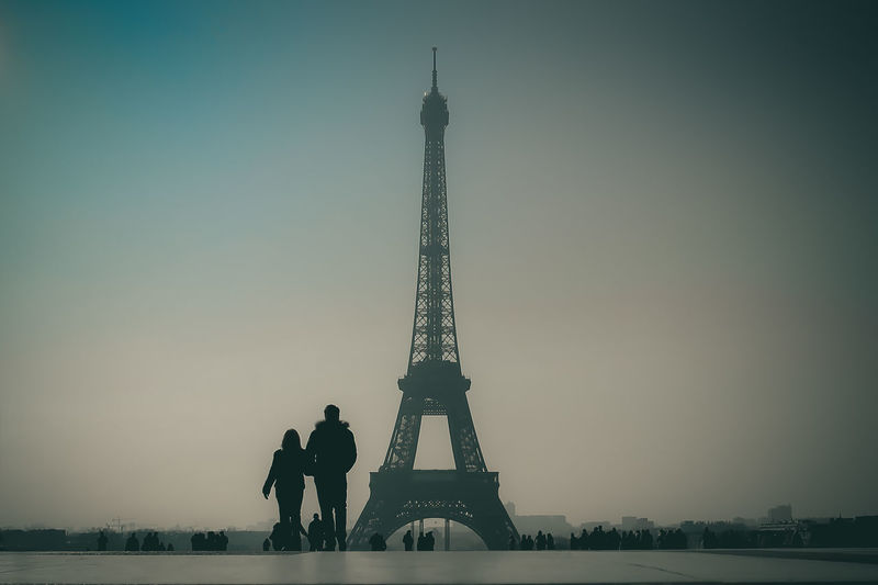 Couple standing against eiffel tower