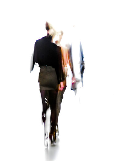Rear view of woman walking against white background