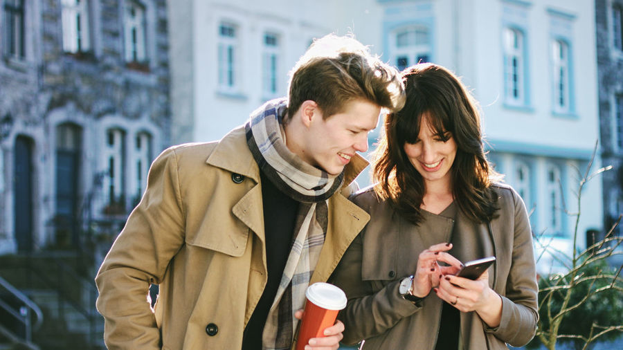 Adult Architecture Brown Hair City City Life Clothing Communication Connection Couple - Relationship Looking Down Mobile Phone Outdoors Portable Information Device Scarf Smart Phone Technology Text Messaging Trench Coat Two People Waist Up Warm Clothing Wireless Technology Women Young Adult