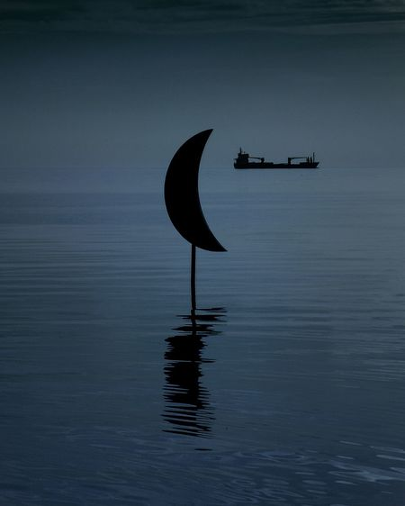 Silhouette boat in sea against sky at dusk