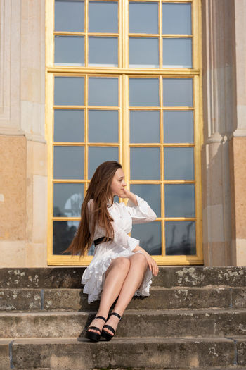 Full length of young woman sitting against window