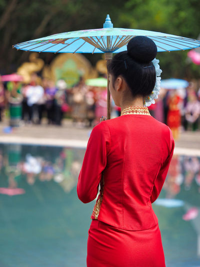Rear view of woman in traditional clothing standing with umbrella by lake