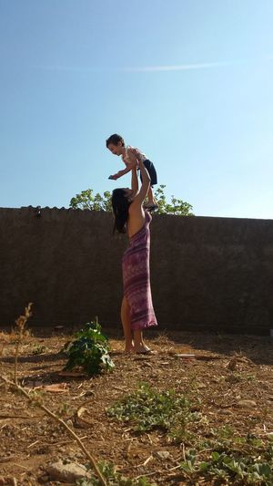 Woman Holding Boy In The Air