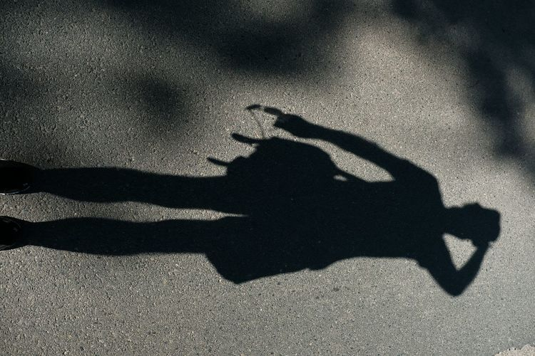 High angle view of silhouette person with shadow on street