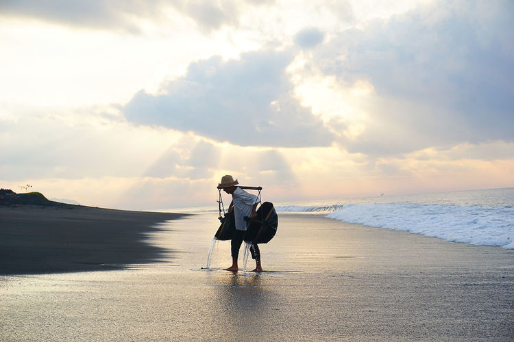 salt farmer working during sunrise Beauty In Nature Casual Clothing Cloud Cloud - Sky Cloudy Day Full Length Horizon Over Water Idyllic Leisure Activity Lifestyles Nature Outdoors Scenics Sea Shore Sky Tranquil Scene Tranquility Vacations Water