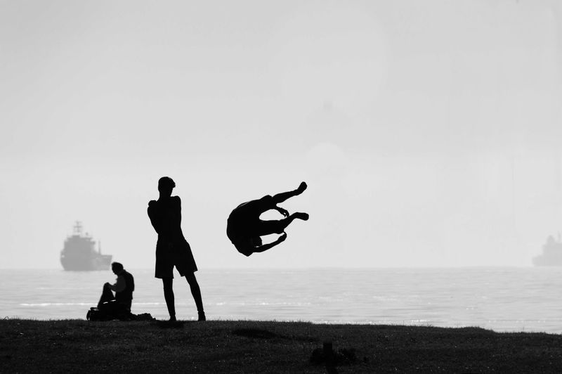 Silhouette man performing stunt at sea shore against sky