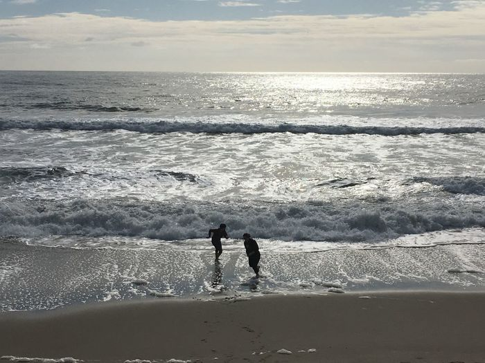 High angle view of silhouette friends running at beach