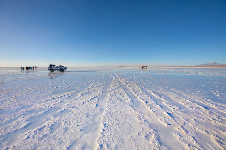 Scenic view of salt flat against clear blue sky
