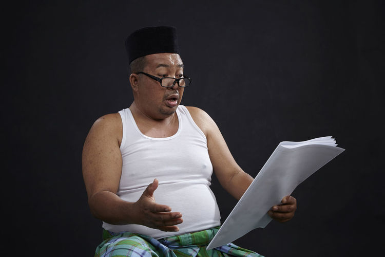 malay ethnicity man with casual clothing wearing songkok reading blank newspaper Funny Happy News Paper Reading Retired Sarong SarongPants Blank Blank Paper Casual Clothing Costume Eyeglasses  Facial Expression Lifestyles Newspaper Old One Person People Person Portrait Real People Relax Singlet Surprise