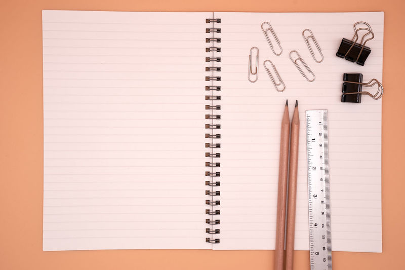 Directly above of blank diary with office supply on brown background