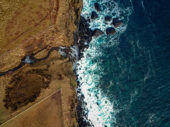 Aerial view of sea with rocky coastline