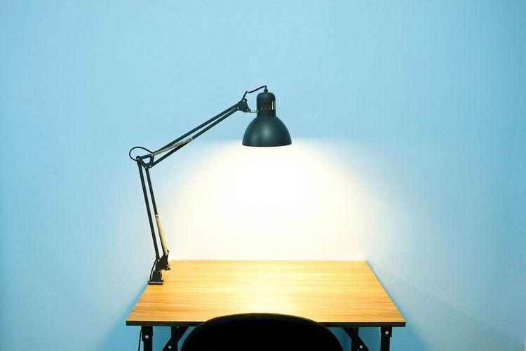 Illuminated lamp on table against wall