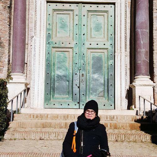 Portrait of smiling woman standing against door