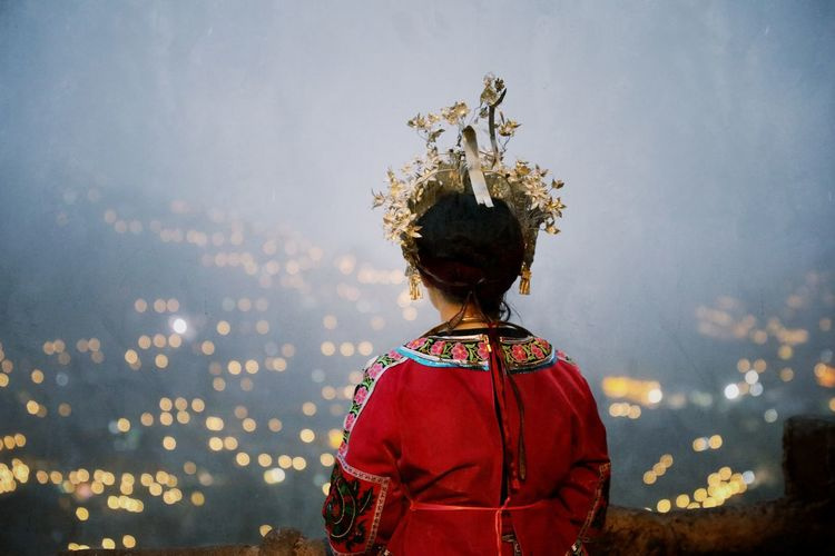 Rear view of young woman in traditional clothing standing against sky