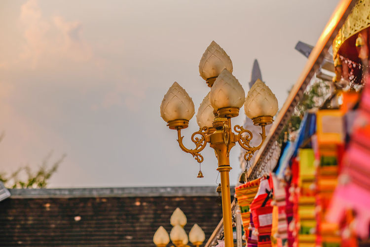 Low angle view of decorations on roof against sky