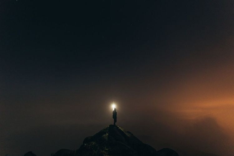 Silhouette Person Holding Light On Top Of Mountain Against Sky At Night