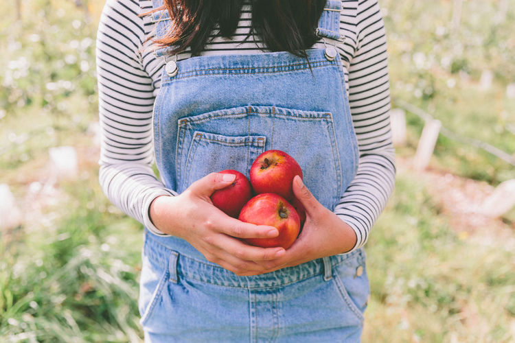 Apple Adult Agriculture Casual Clothing Close-up Day Food Food And Drink Freshness Front View Fruit Healthy Eating Healthy Lifestyle Holding Leisure Activity Lifestyles Low Section Nature One Person Outdoors Overalls People Real People Standing Women