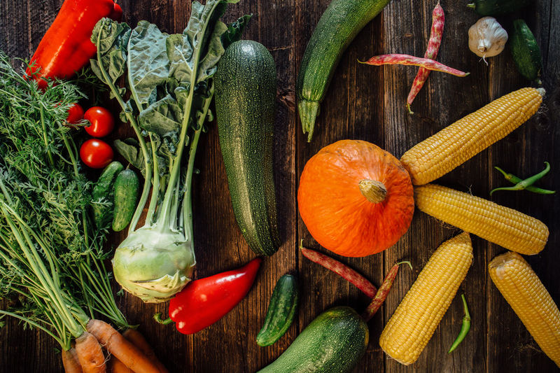 High angle view of fresh vegetables on wooden table Chili Pepper Corns Food Freshness Harvest Healthy Food High Angle View Horizontal Kohlrabi No People Organic Pumkin Raw Food Red Red Chili Pepper Vegetable Vegetables Wood Table