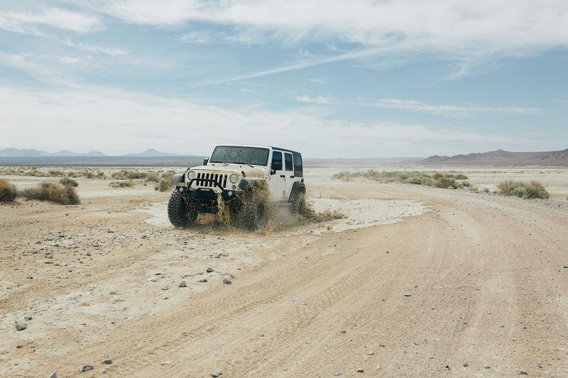 Dirt road in desert against sky