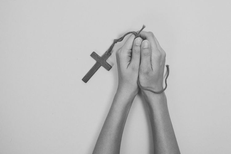 Cropped hands holding rosary against gray background