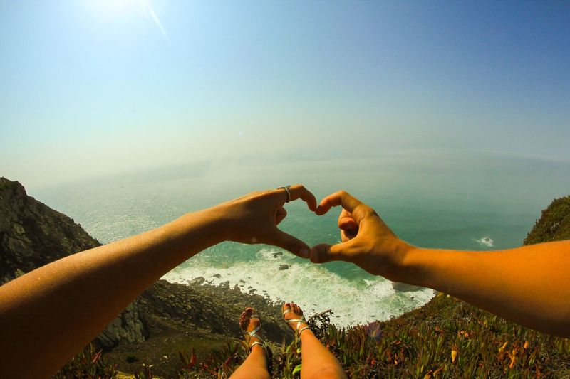 Close-up of couple making heart shape on mountain by sea